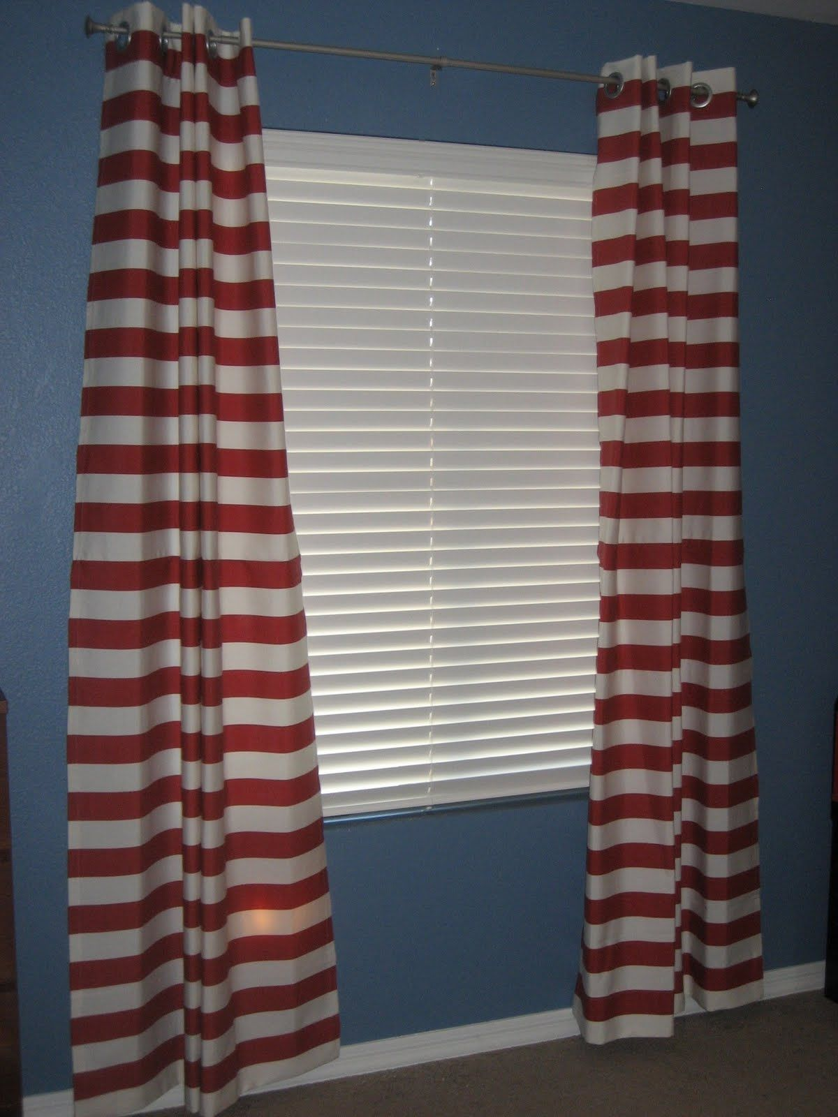 With grey wall maybe navy white stripe curtains instead w red pops of color