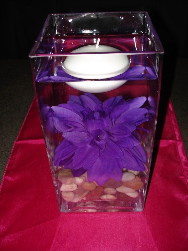 purple flower on river rocks in water with floating candle baby