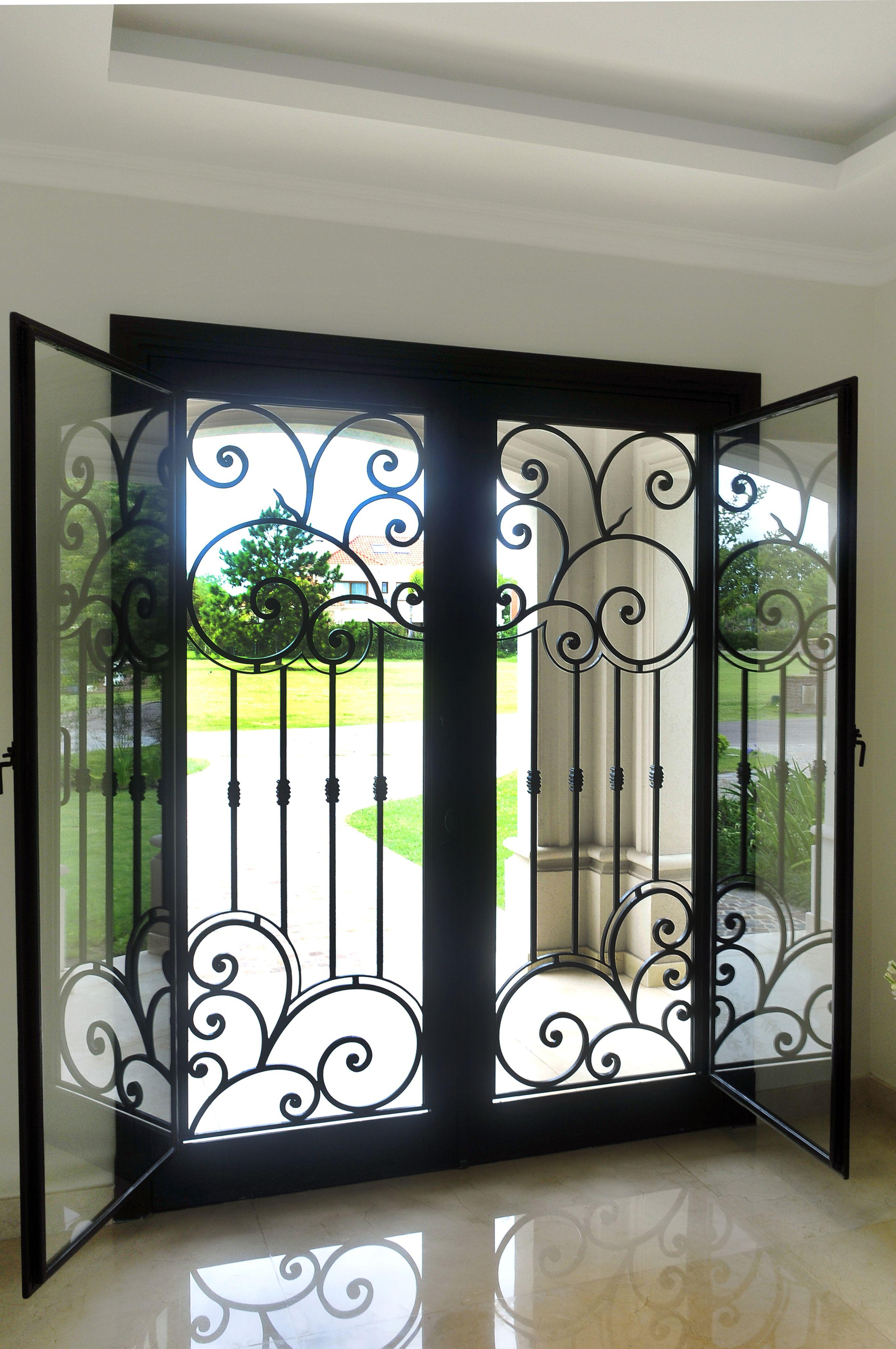 puerta de hierro forjado con postigos de vidrio