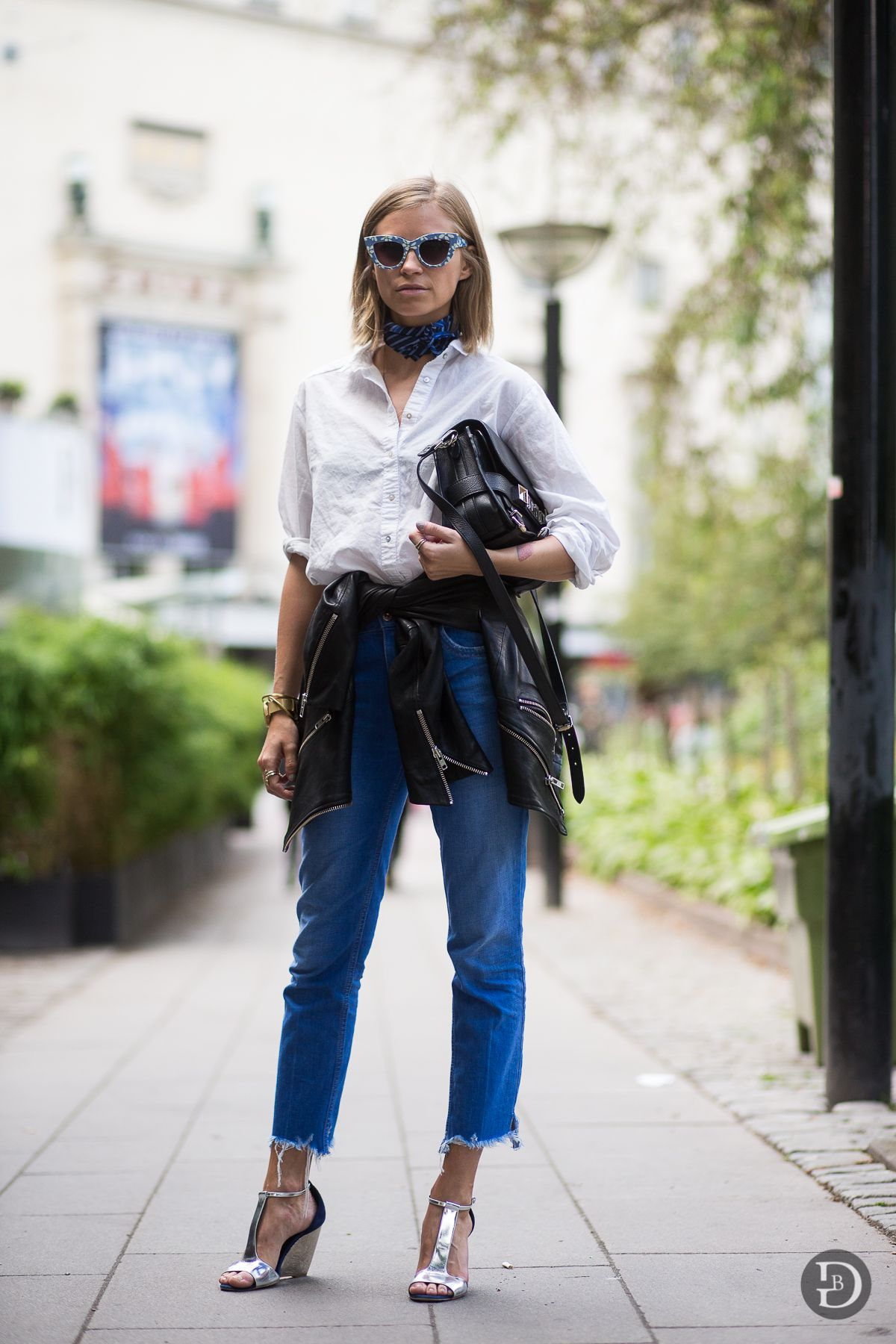 Tie a leather jacket around your waist to toughen up a classic button down and jeans combo. A scarf (the go-to accessory of the season) and statement sunglasses wake up the look.    - ELLE.com