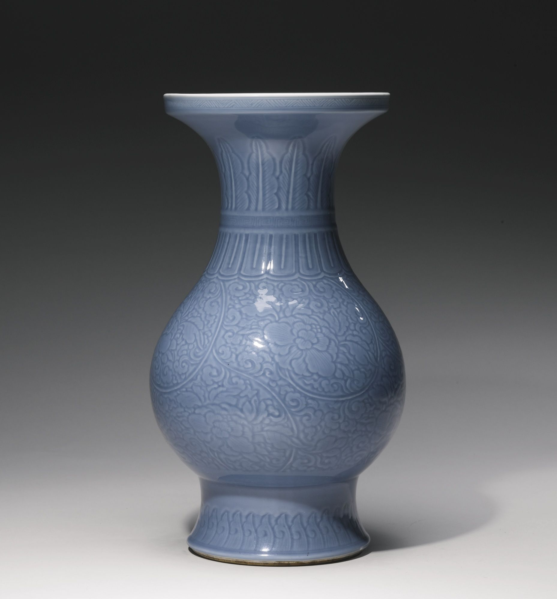 A CARVED BLUE-GLAZED 'PEONY' VASE  QING DYNASTY, KANGXI PERIOD the baluster body rising from a short spreading foot to a tall trumpet neck, carved around the exterior with peony scrolls between lotus, ruyi and stiff leaf bands, covered overall with a pale lavender-blue glaze, the interior and base glazed white, apocryphal six-character Chenghua mark in underglaze blue  Height 15 1/8  in., 38.5 cm