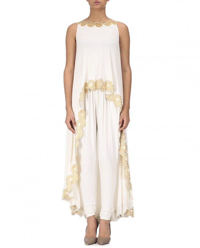 Ivory asymmetrical top with golden new wave design featuring a high neckline with a golden new wave pattern at the front and back neckline. Sleeveless. Asymmetrical hemline with golden new wave pattern at the hemline.   Wash Care : Dry Clean Only.  Matching white cowled pants included.