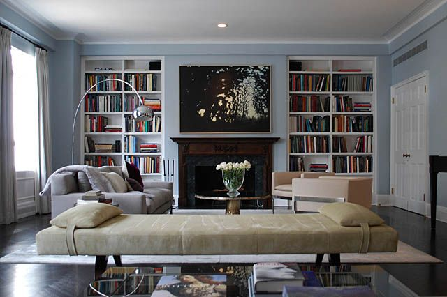 Symmetrical bookshelves, large art over fireplace, low furniture ...