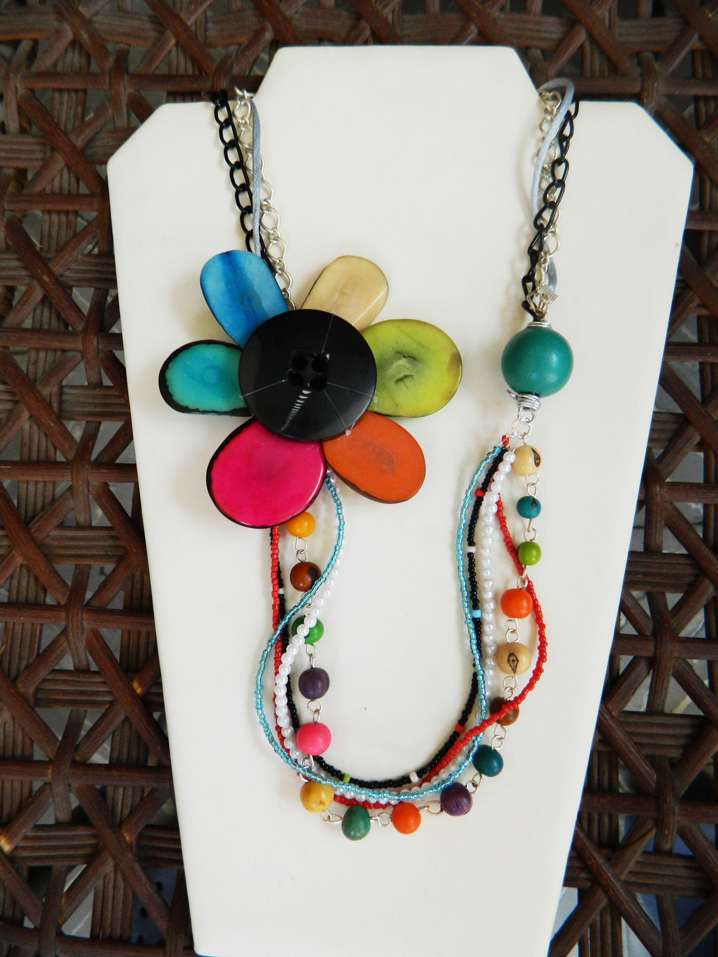 Collar hecho con un botos negro, cadena, semillas de tagua de diferentes tamaños, y mostacilla