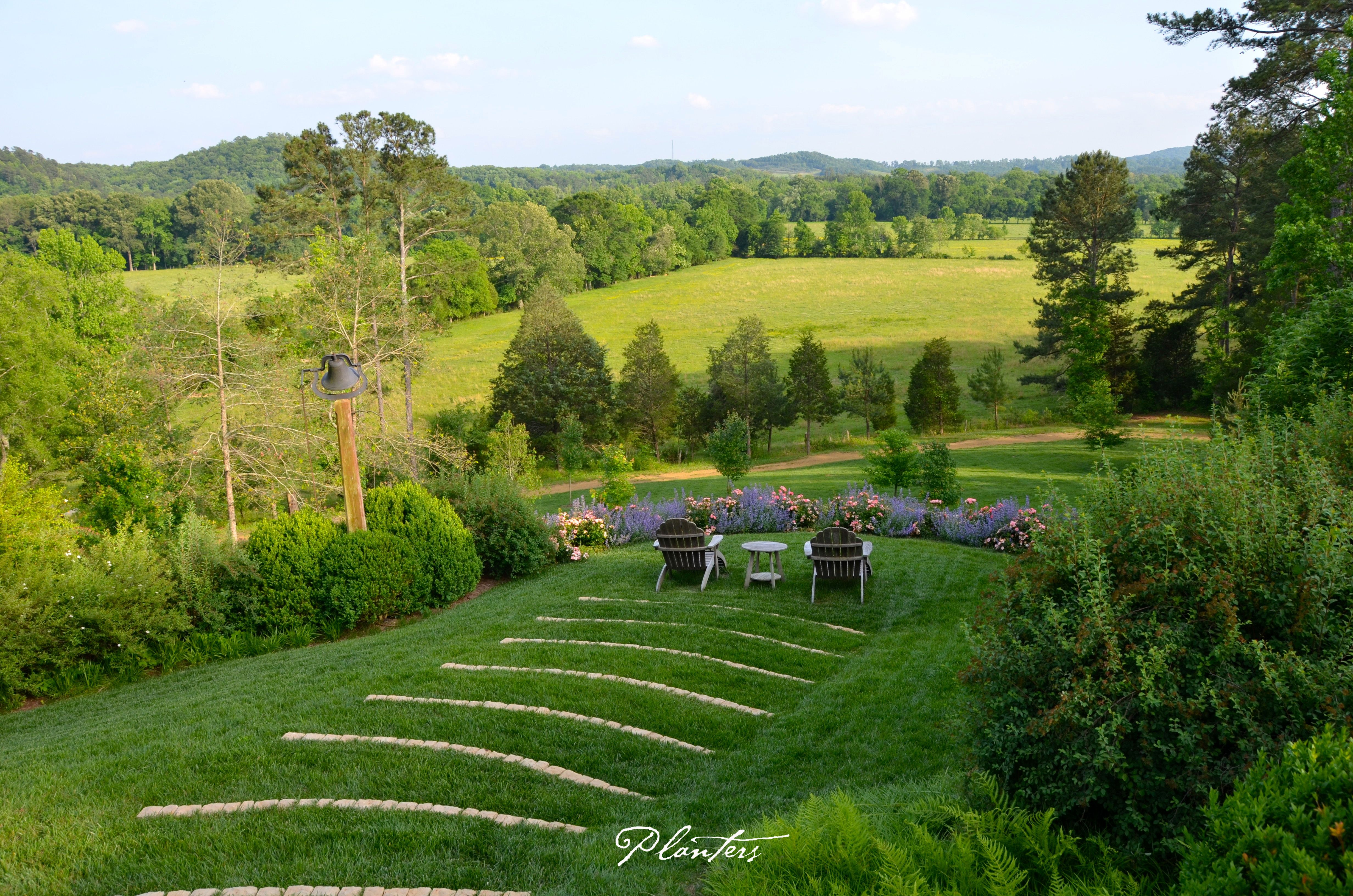 Stairs set in the lawn leading to an overlook with a garden and adirondack chairs. A Planters Design. Rome, GA