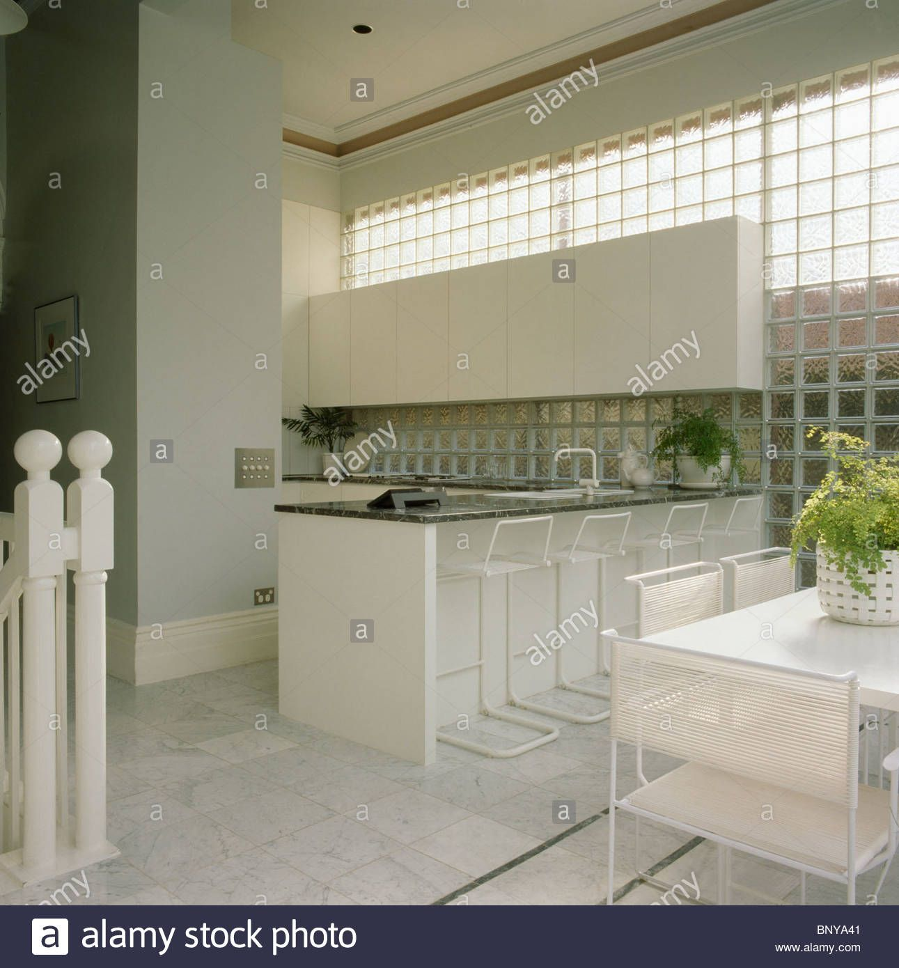 glass-brick-wall-in-modern-kitchen-dining-room-with-white-stools-at ...