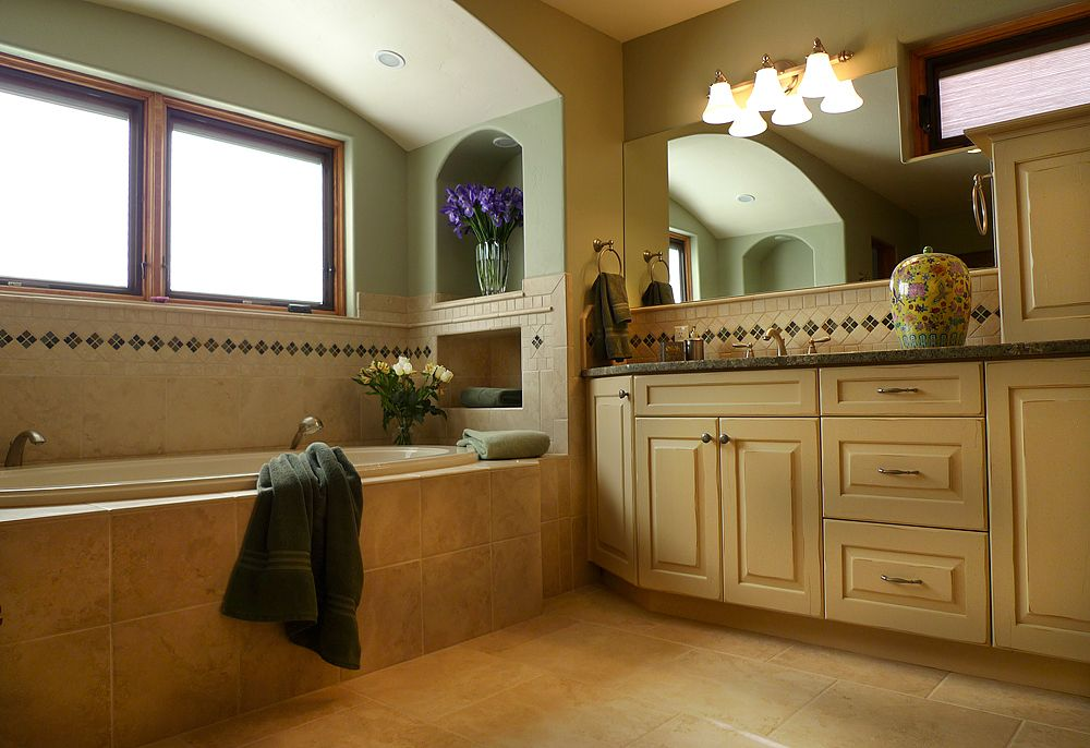 Elegant master bath with large soaking tub and distressed white painted cabinetry