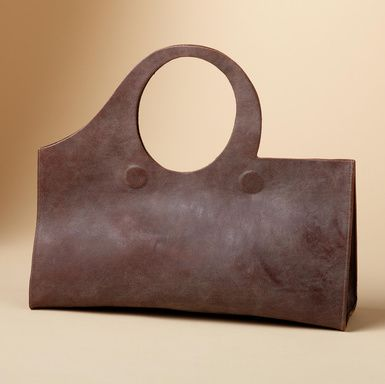 "Sculptured swag bag in unlined, vegetable-tanned leather, hand aged to a deep tan patina, asymmetrically cut with a circular handle, closed with double magnets. Handmade in USA by CYDWOQ. 16""W x 4-1/2""D x 13-1/2""H."