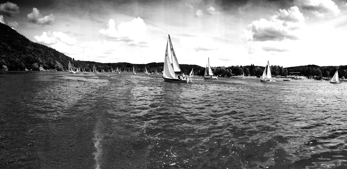 Black and white photograph portraying sailing boats on a river