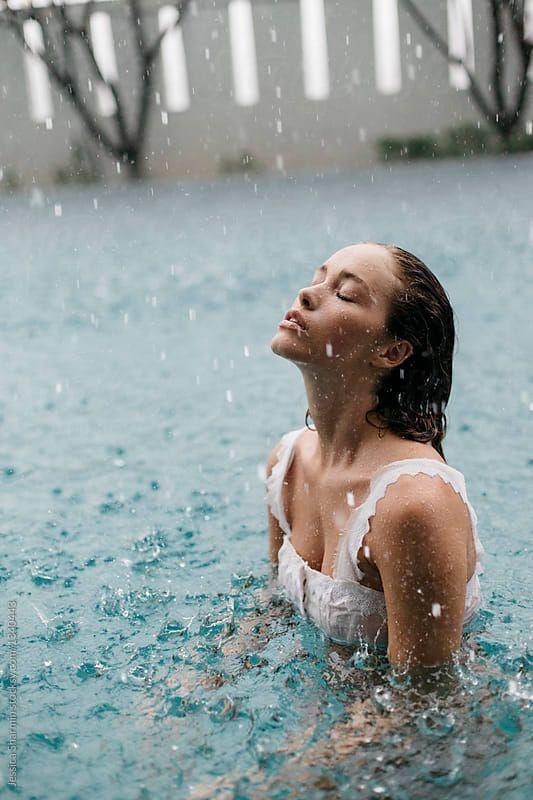 Frau in einem Pool schwimmt im Regen von Jessica Sharmin für Stocksy United – … – Oriel D.