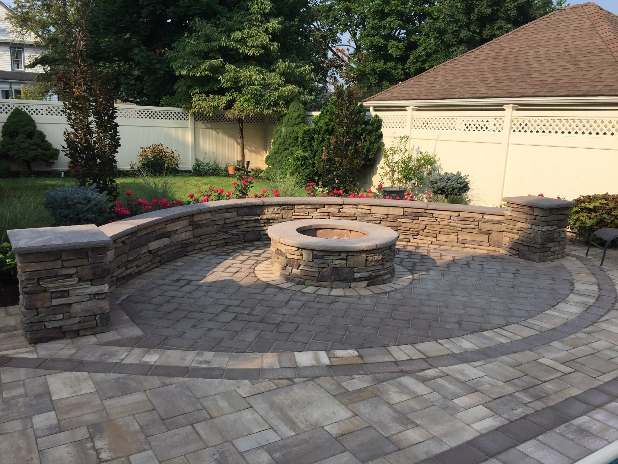 Paved Patio With Stone Veneer Sitting Wall Circular Fire Pit As Well As Grey Herringbone Pavers All Desi Fire Pit Landscaping Garden Fire Pit Small Fire Pit