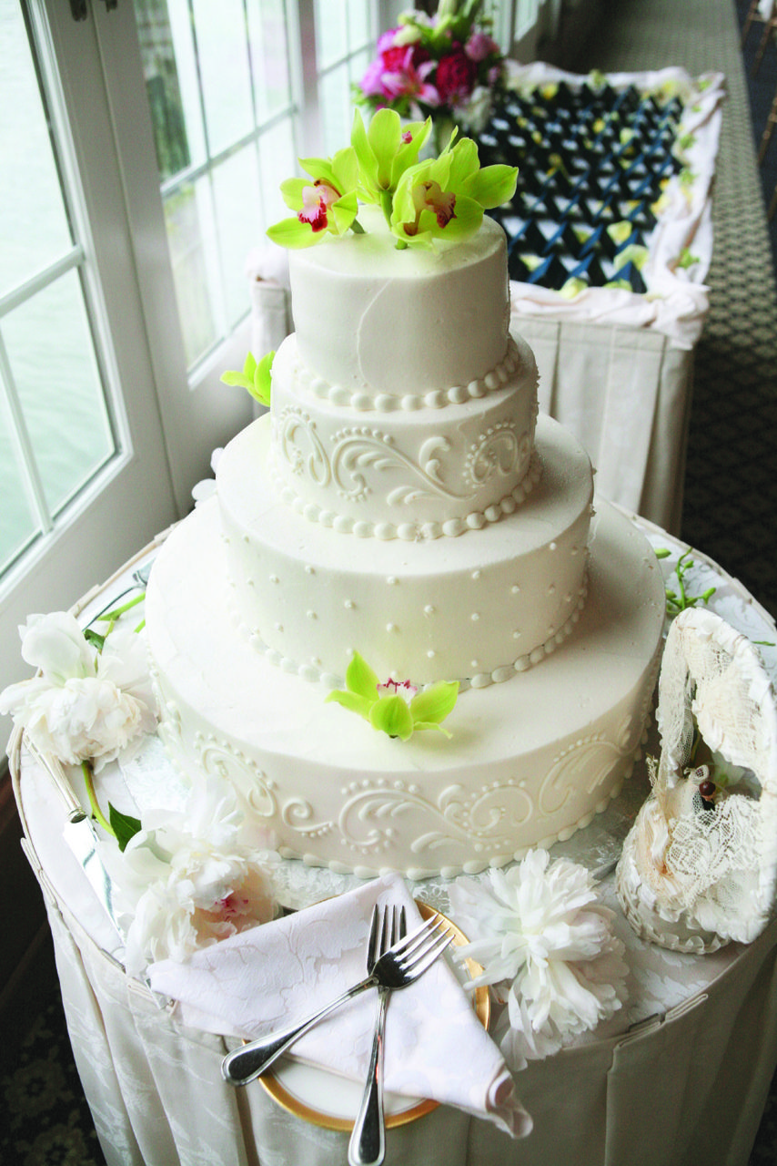 Ivory wedding cake decorated with a white scroll design cake