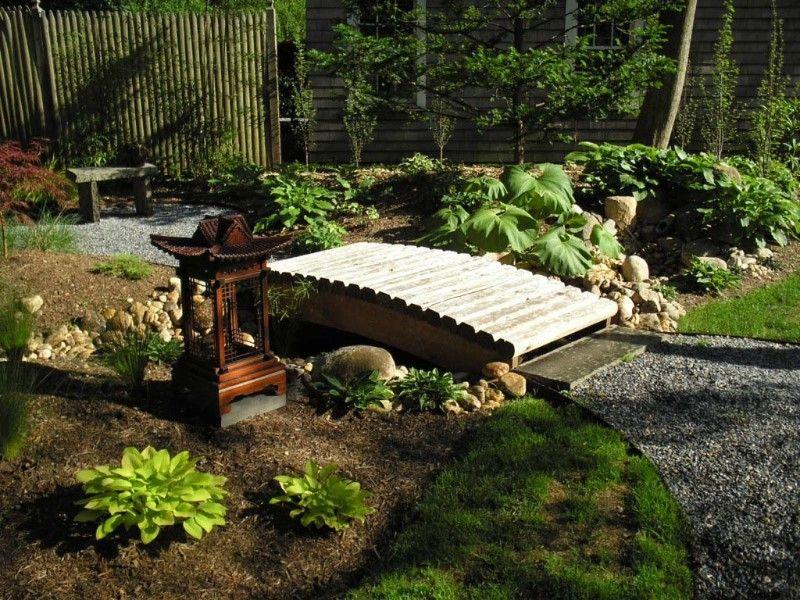 japanese garden bridge in a simple outdoor design with a wooden lantern