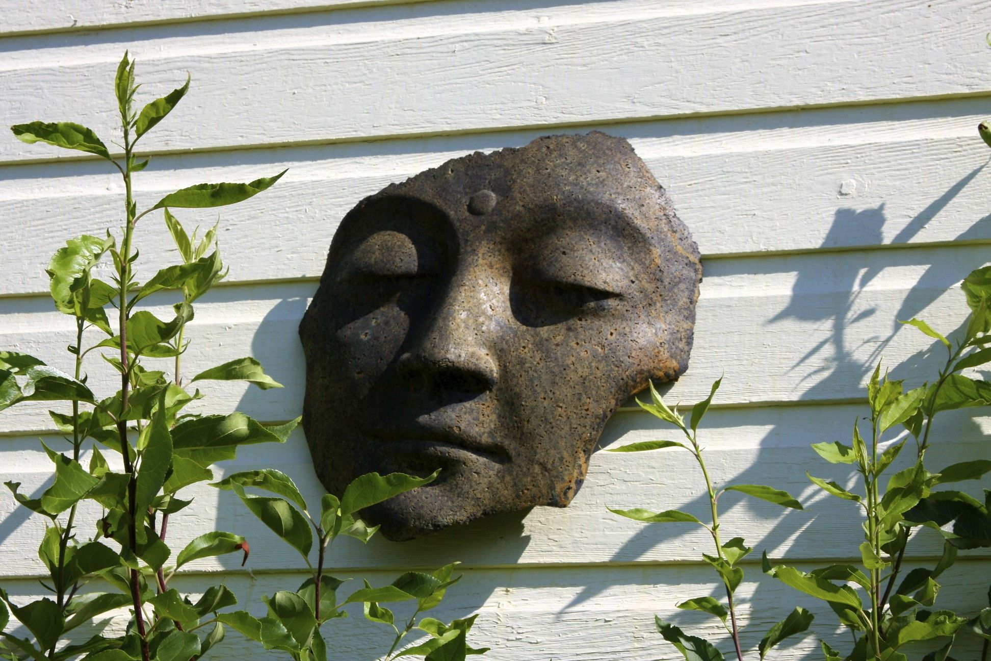 Face on garden studio wall. Photo by Suzann Sladcik Wilson