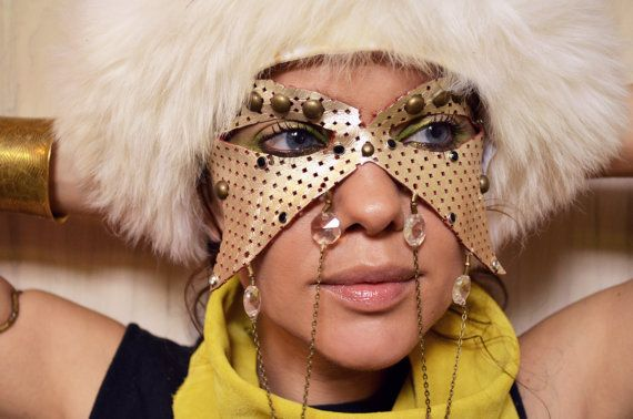 """""""She is certainly a daughter of France.""""  Handmade leather mask. Painted metallic leather is perforated and breathable, and painted metallic. Adorned with brass studs and rhinestones, antique brass chains with Swarovski crystals and shells."""