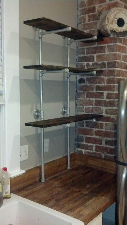 "Galvanized pipe with ""aged"" pine shelves...use chain,claw hammer, nails to scratch surface, get your aggression out...then burn lightly in spots to give it character...stain of your choice.....for the extra cookbooks in kitchen...about $40"