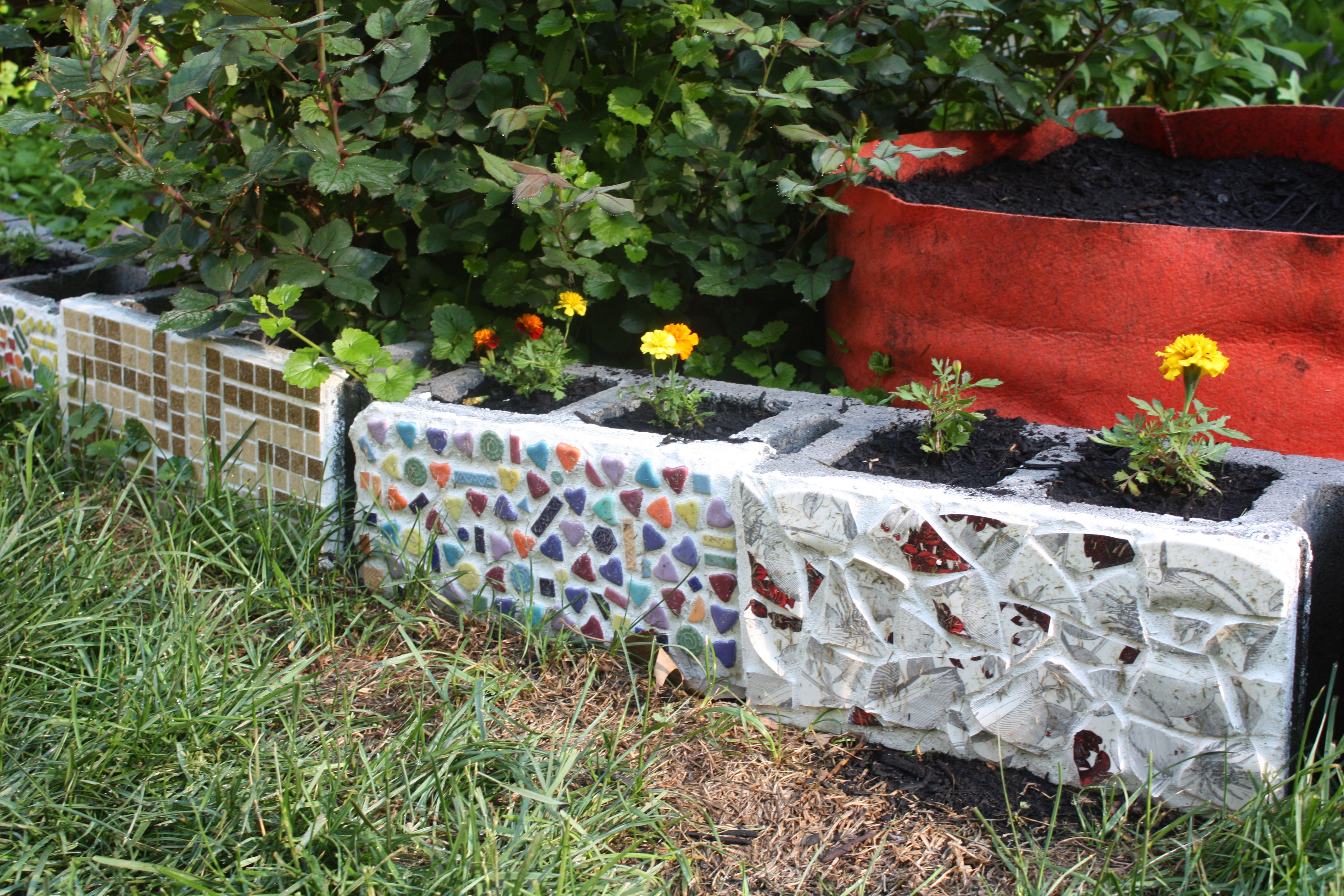 Cinderblock Mosaics Done With Broken Dishes And Tiles Portulaca Marigolds Planted Along Edge Of Back Garden 5 Mosaic Garden Art Mosaic Garden Mosaic Pots