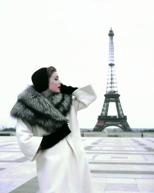 Suzy Parker at the Eiffel Tower wearing a winter ensemble by Givenchy in a 1954 photo by Georges Dambier for ELLE magazine