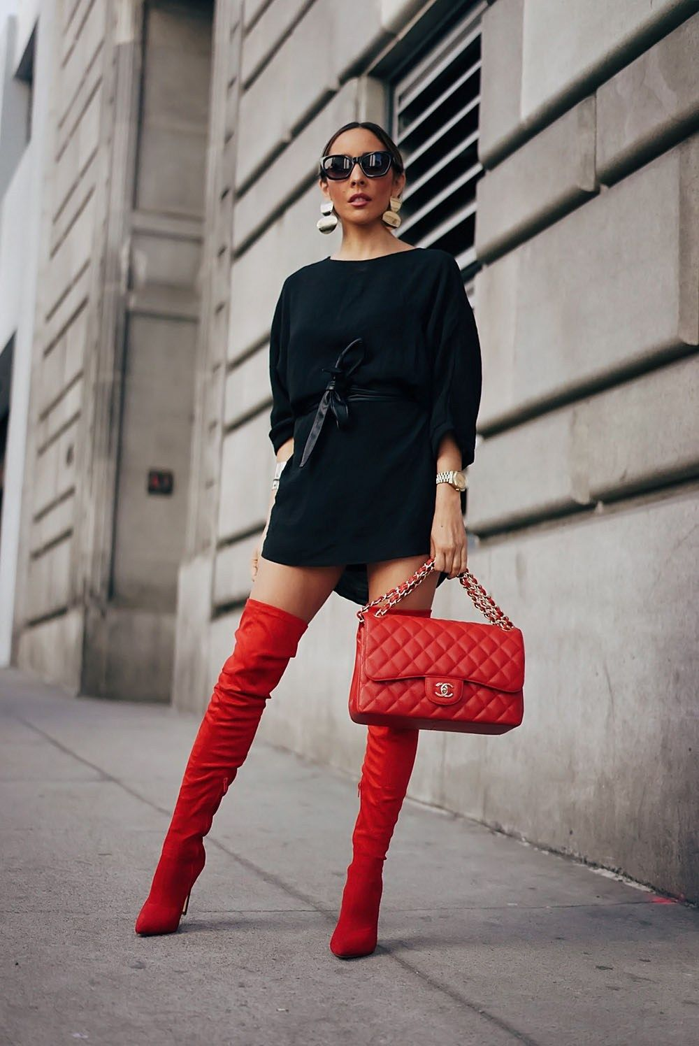 3da82b68aedd Maria De La Cruz wearing a pair of red thigh high boots paired with a black  tunic dress and a red Chanel bag.