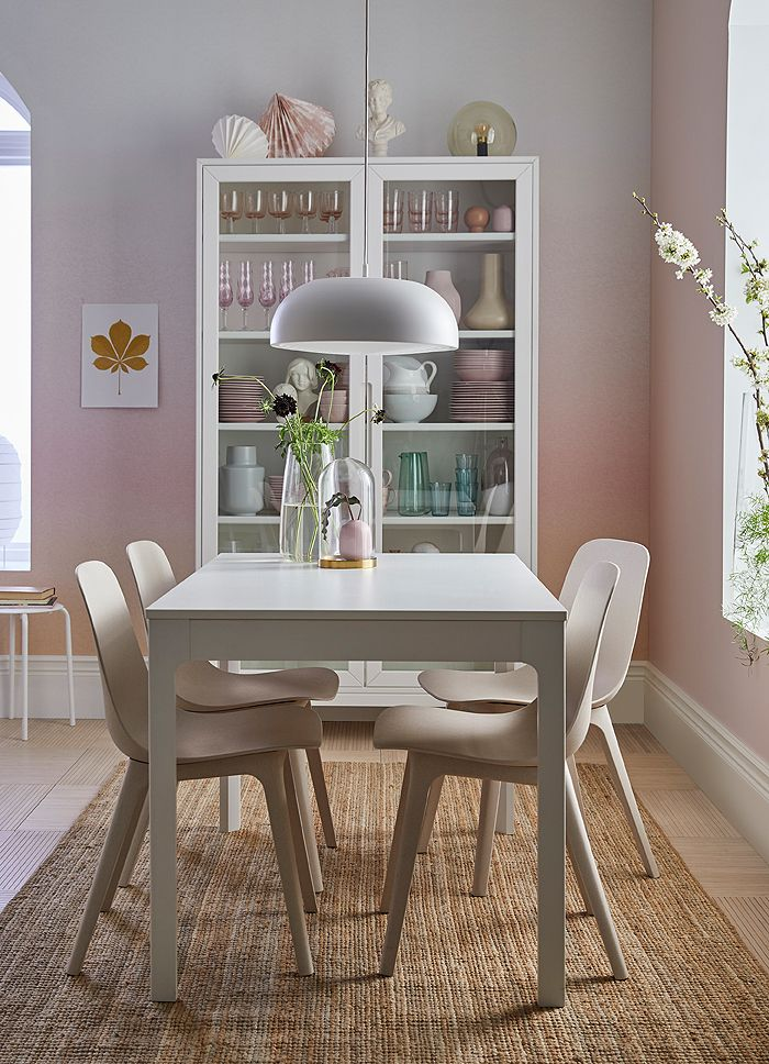 A pink and white dining area with white EKEDALEN table surrounded by