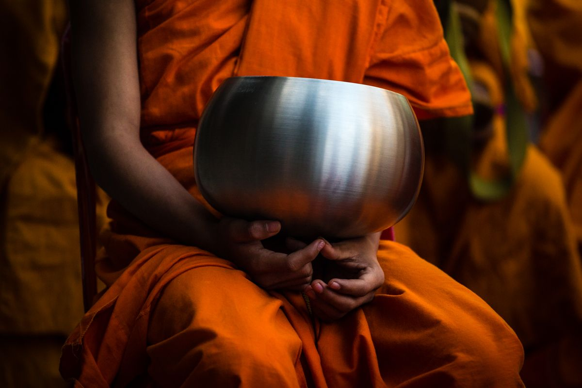 A novice Buddhist monk holds an alms bowl as he attends a