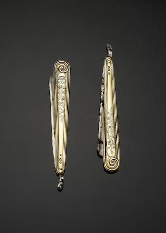 A William IV pair of silver-gilt cut throat razors, by Paul Storr, London 1836, conventional form, with engraved foliate decoration and engraved with a crest and a crown, the steel blades by Paget of 195 Piccadilly