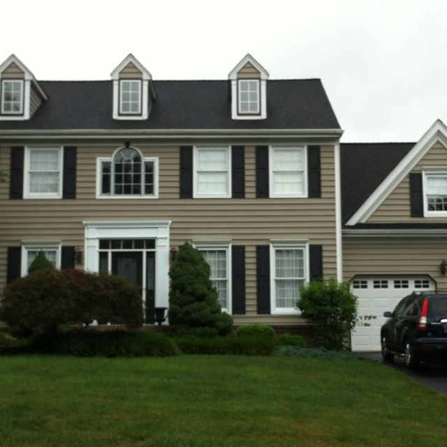 Black Shutters And Black Detailing In White Windows Tan House