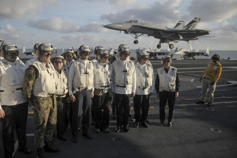 Ukrainian Prime Minister Arseny Yatseniuk (4th L) and Defence Minister Stepan Poltorak (3rd L) stand on the flight deck of the nuclear-powered aircraft carrier USS Harry S. Truman at the at an undisclosed position in the Mediterranean Sea
