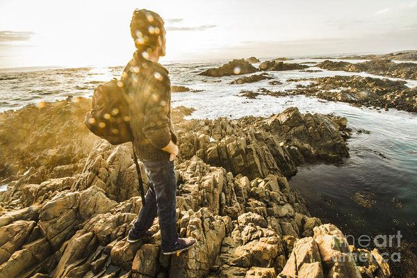 Creative retro picture of a happy young man enjoying the peaceful calm of a tasmanian sea getaway. Real life sun flare capture by Ryan Jorgensen