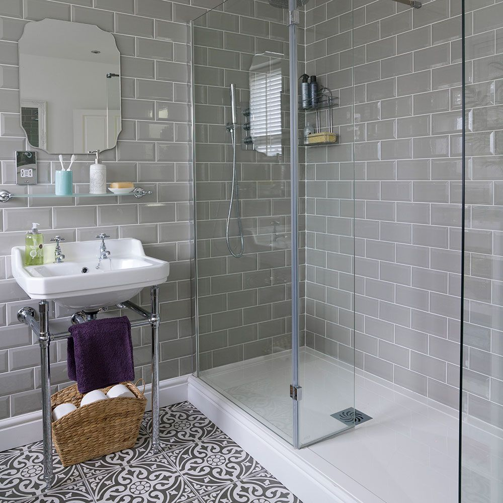 Bathroom with roll-top bath and patterned floor tiles