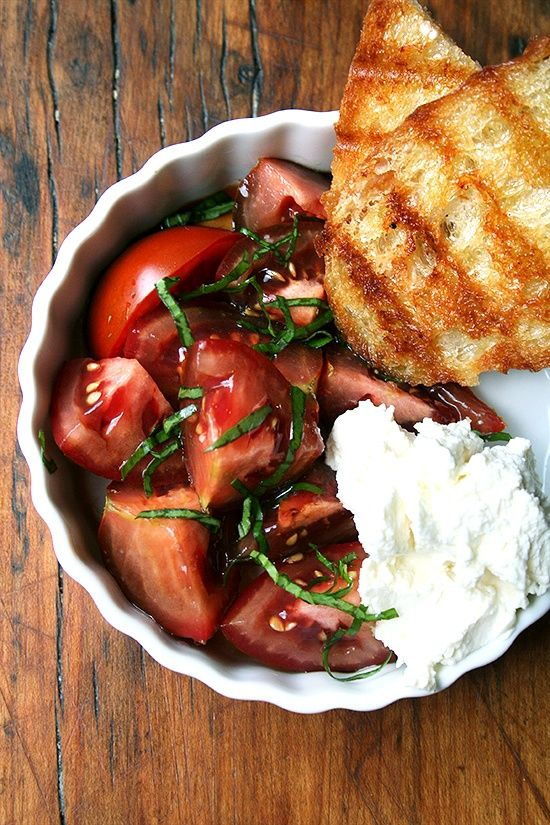 Tomato & Ricotta Salad.  Cut tomatoes into nice chunks and place in a bowl. Season with salt. Drizzle with olive oil and balsamic. Toss with fresh basil. Place in a bowl with a nice dollop of fresh ricotta on the side.  Heat a grill or grill pan. Brush with olive oil. Grill bread until nice and toasted. Serve along side your salad and cheese.