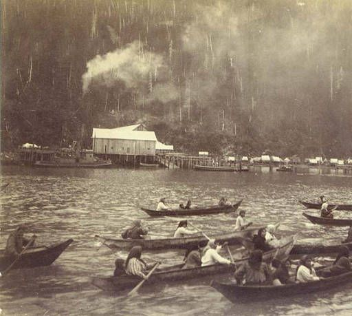Photo of Tlingit women in canoes with coastal town in background, Alaska, between 1898 and 1900