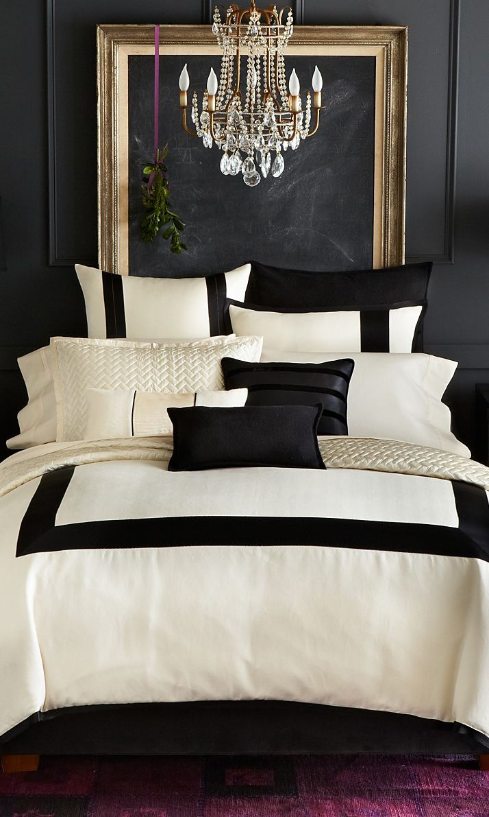 Super sophisticated, luxurious cream and black bedding against a pure black wall...