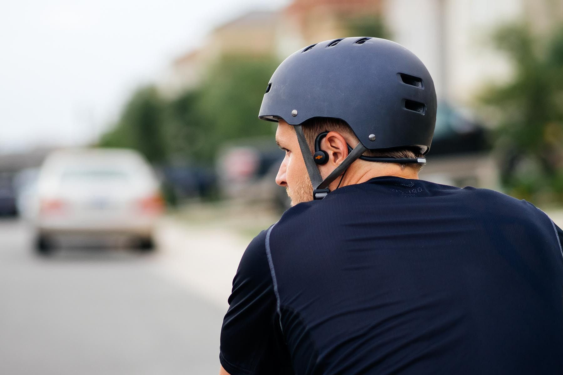 Man cycling down a street wearing Sports M 3 bone conduction wired headphones under his safety helmet.