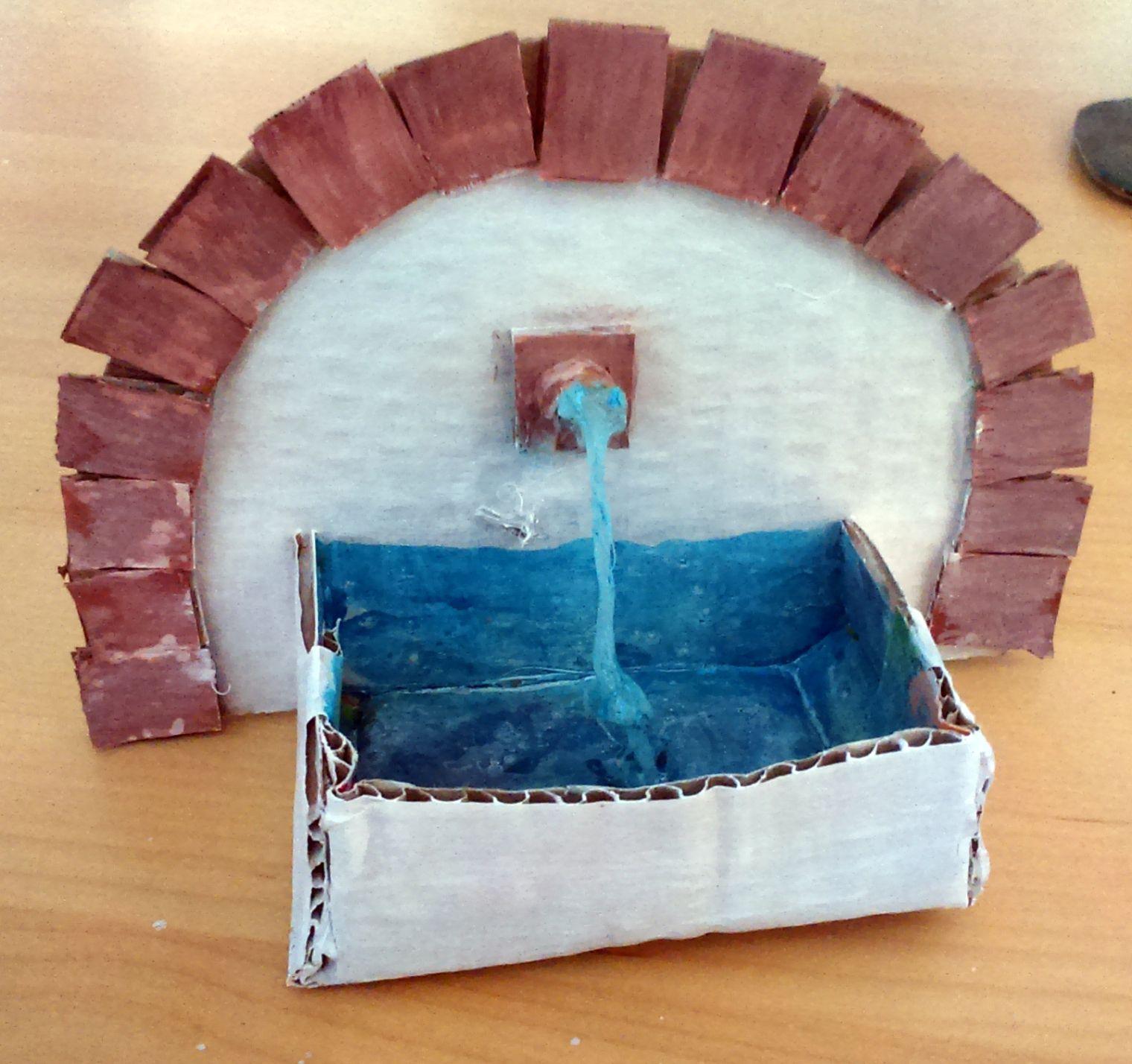 """Una pequeña fuente de agua, muy sencilla. Una """"pared"""", con algunos trocitos de cartón pegados para darle como la idea de ladrillo, un pequeño grifo y el agua. hecha con pegamento de sil…"""