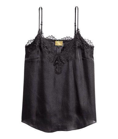 Black. Satin camisole top. Narrow, adjustable shoulder straps, V-neck, and wide lace trim at upper edge. Slightly longer at front.