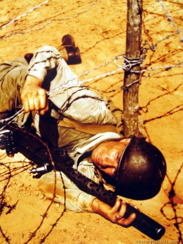 Soldier crawling through barbed-wire entanglement with this machine gun while on maneuvers.