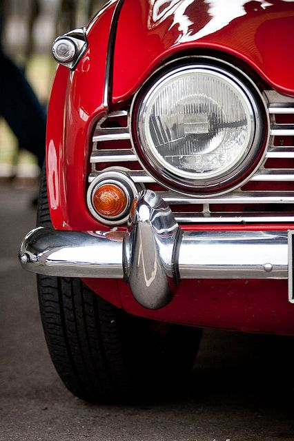 Triumph. Likely a TR4. Love the chrome and red paint.