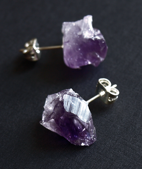 """Handmade raw amethyst chunk stud earrings. Approx. 1/2"""" long chunks of raw, naturally variegated amethyst. Silver metal posts with backs. Lightweight and low key, but still funky. Stones will vary naturally from earring to earring. Several different pairs of earrings are seen in the pictures; you will receive one of the pairs. Amethyst; silver metal posts and backs By Adam Rabbit. Handmade in Arizona"""