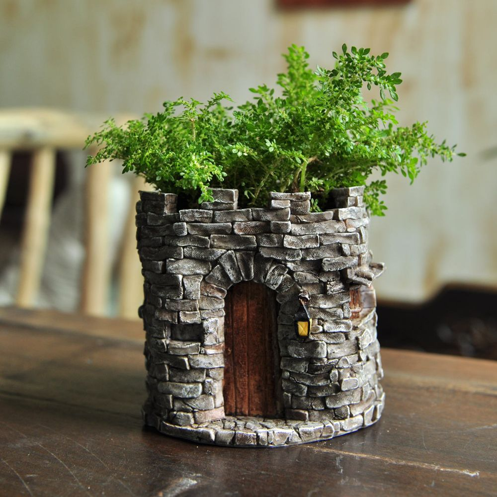 Fairy Castle Flower Pot is part of Big garden Castle - description~ Forget boring flower pots in your garden  With this fairy castle flower pot, you can turn even the most boring ferns into magical worlds  The pot is designed to look like the base of an old castle  It is features  stone  walls built into a turret shape, and in one side is an elegant old arch into which a rustic wooden door has been fitted  There is an old carriage lamp, a low wall at the top and a few narrow windows to make this a wonderful spot for a fairy or other garden resident ~ dimensions~ 4 25  Wide x 4  Deep x 4  High~ materials~ Resin~