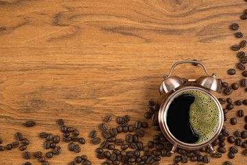 coffee background of hot black coffee with foam in alarm clock cup wooden table with roasted coffee beans scattered around in concept of coffee time ,