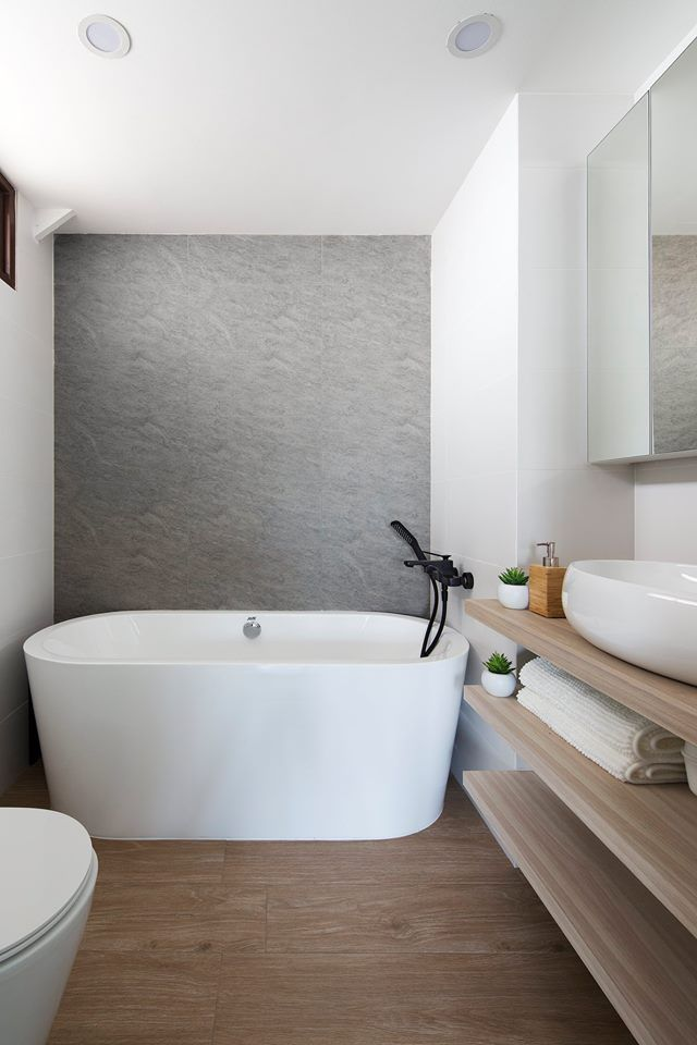 A large standalone bathtub sits in this contemporary bathroom ...