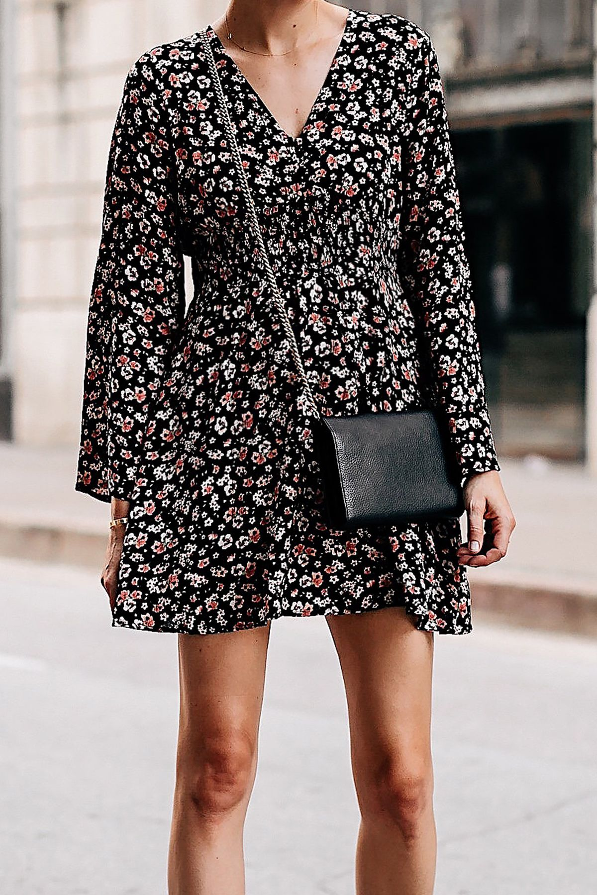 Blonde woman wearing black floral long sleeve mini dress gold chain