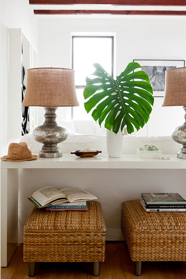 burlap mercury glass lamp, white vase with single split-leaf philodendron, white console, seagrass stools
