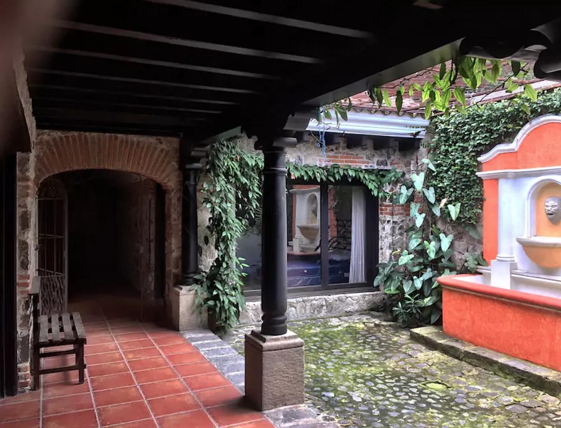 Patio central estilo colonial, paredes de piedra y