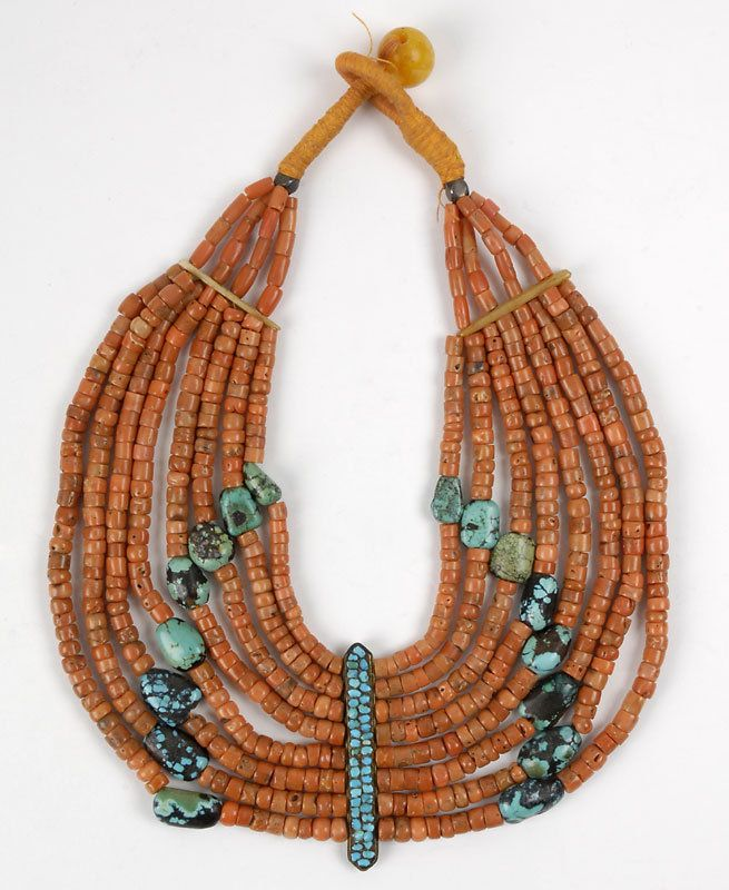 Ladakh | Old Himalayan Woman's necklace; Eight strand necklace held together by two bone and a central metal clasp decorated with turquoise smithereens. Made of differently colored and sized turquoises between coral beads. Finished with a circular amber bead | ca. pre 1950