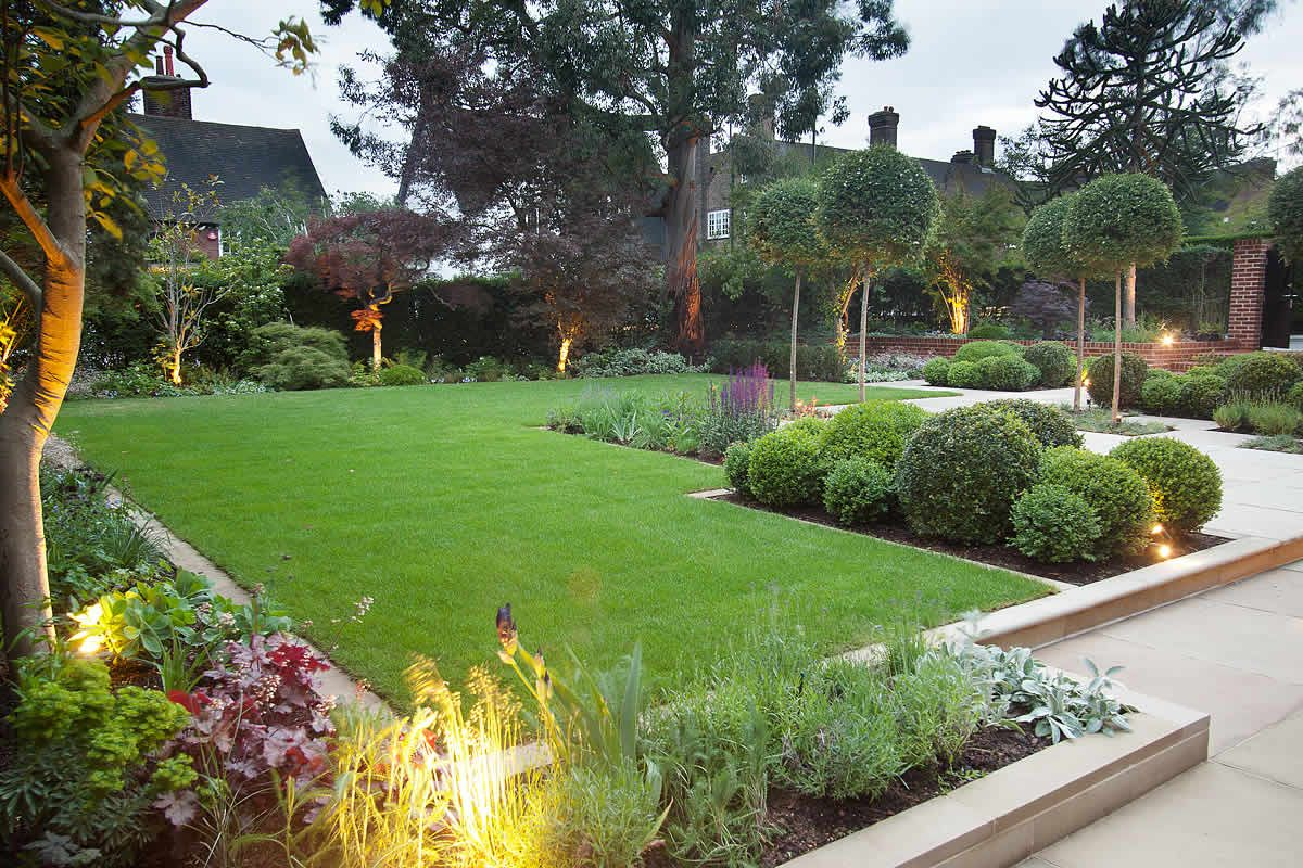 landscape gardener design a structured and somewhat formal garden design with neat edged lawns containing varied hedging and shrubs along the borders