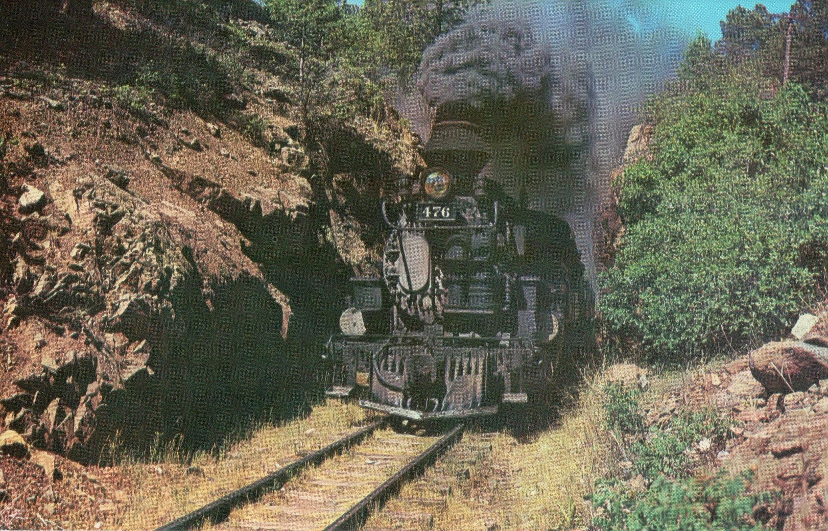 The Silverton Narrow Gauge in the Rockwood Cut.  This historic last narrow gauge train, using some of the original passenger cars built in 1882, roars through the Rockwood cut towards the HighLine above the Animas River.  Modern chrome card.