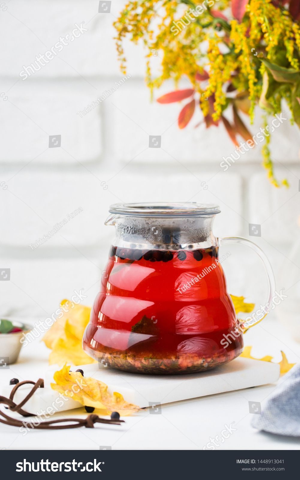 Hot bright autumn drink in a teapot. Tea with taste of ginger, sea-buckthorn, po...