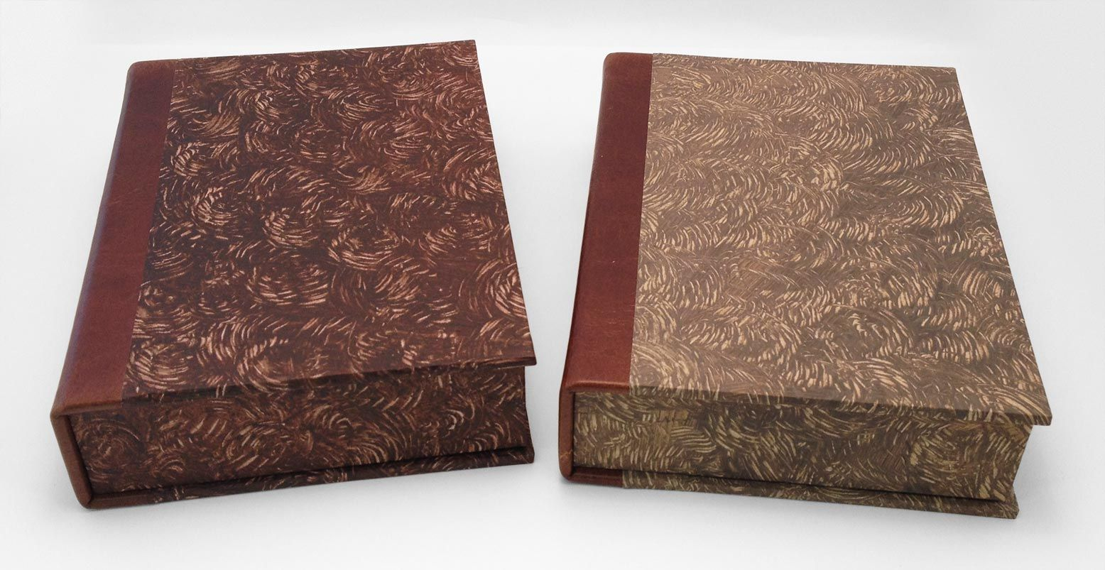 Leather clamshell boxes covered in handmade paste paper. Boxes are made to house handcrafted wooden chess pieces.